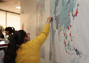 A woman placing a marker on a wall map of Asia that shows where the participants come from.