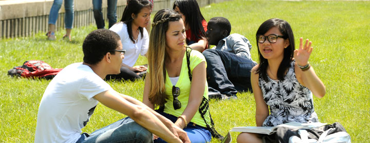 BHCC students sitting on the lawn having a conversation and relaxing in the sun.