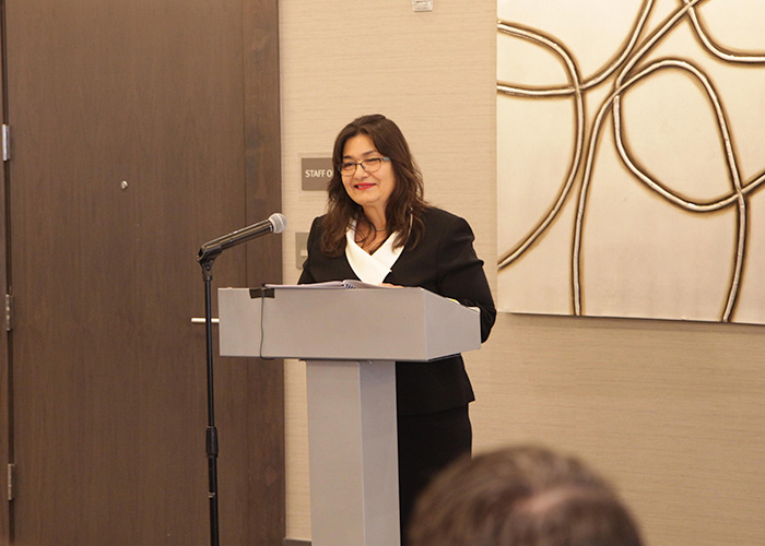 Alice Murillo speaking at a podium