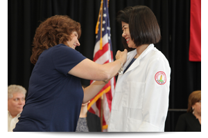 thumbnail of a student receiving her pin