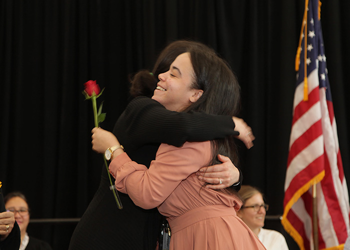 student hugging a faculty member on stage