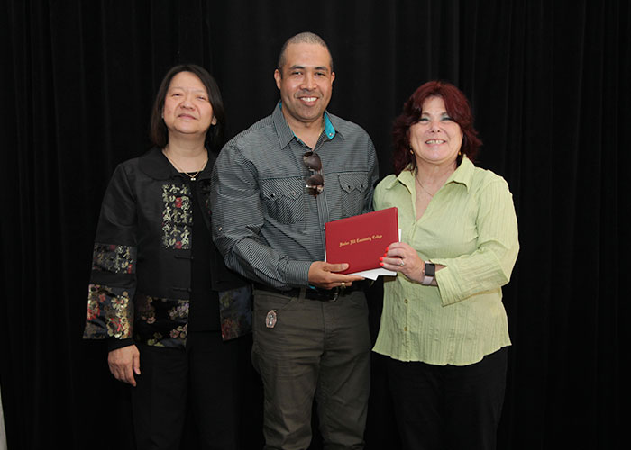 male student receives diploma from Toni and president eddinger