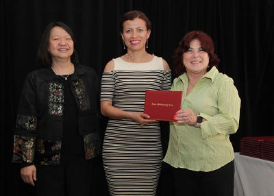 female student receives diploma from Toni and president eddinger