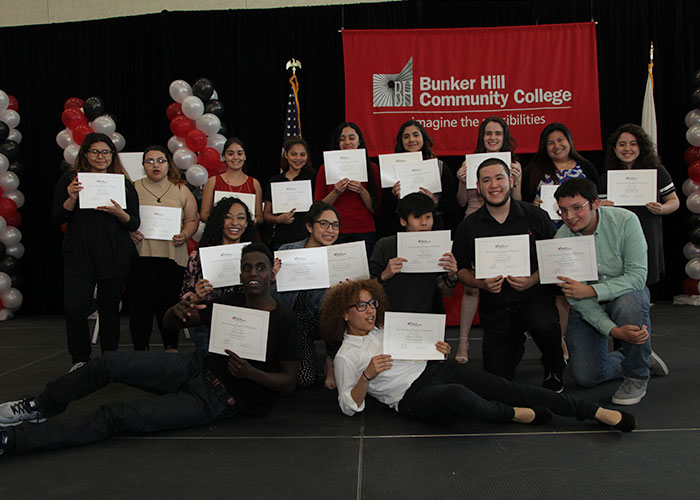 larger group of students posing with their certificates