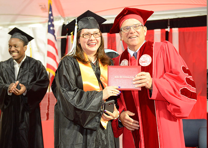Bill Walczak gives student a diploma
