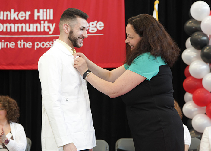 male student receiving his pin from faculty member