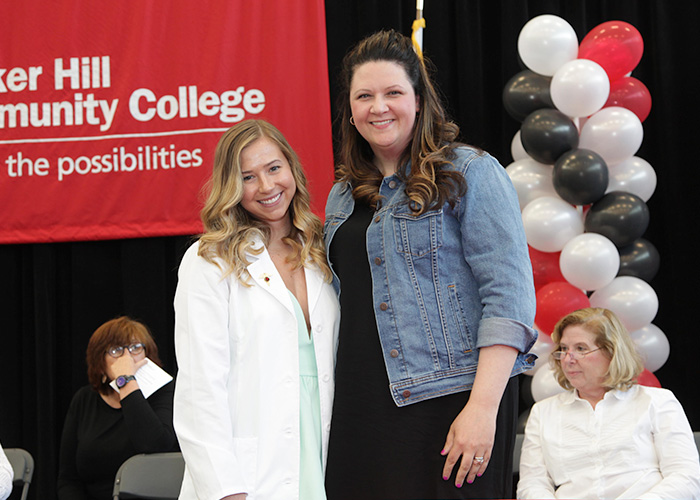 female student posing with faculty after getting her pin