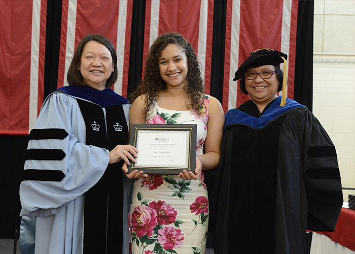 female awardee with president and dean puente