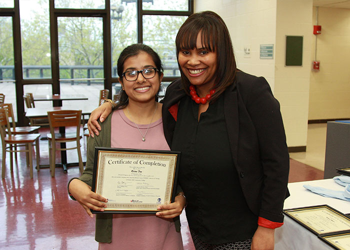 Student posing with certificate with Latoya Robinson