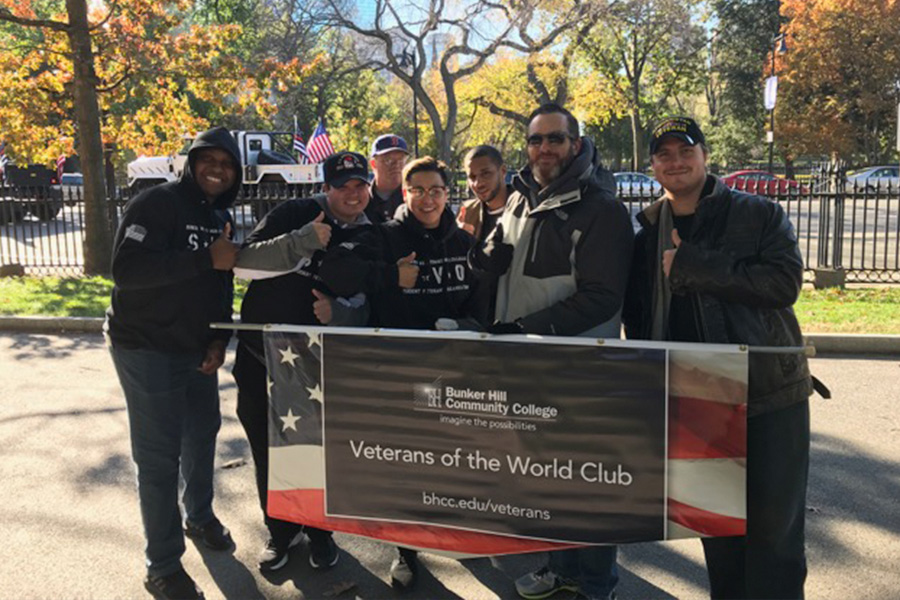 BHCC Veterans and staff posing with their veterans day parade banner