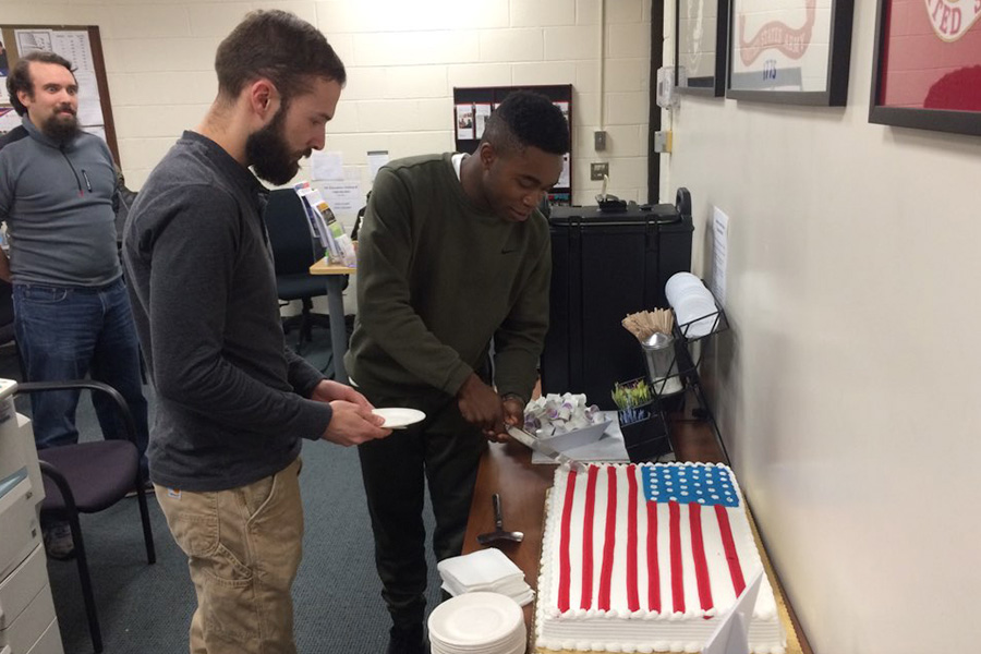 Two Veterans cutting an american flag cake