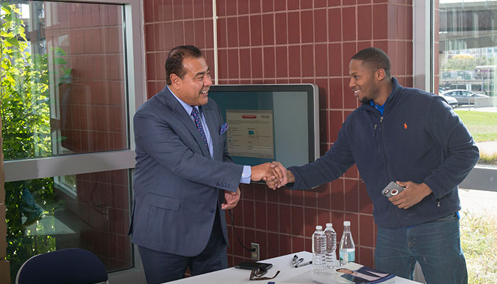 John Quinones shakes the hand of a BHCC student during his meet and greet on October 14, 2016