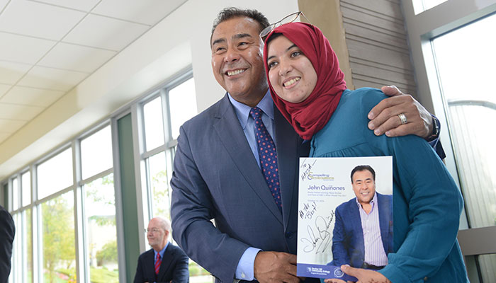 John Quinones poses for a picture with a student