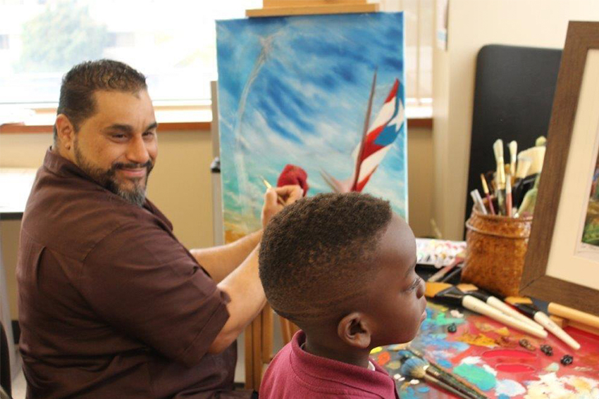 artist painting at an easel with a child next to him