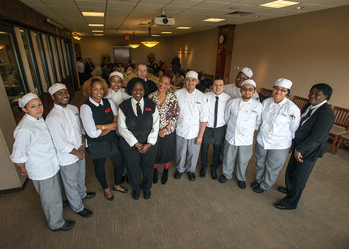 Terry McMillan in the culinary arts dining room with students
