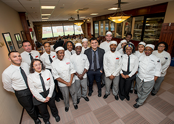 Jose Vargas posing with the students of the culinary arts dining room